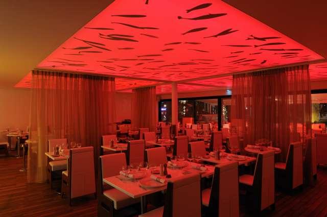 Salle de restaurant de l'auberge du port ayant un éclairage rouge.