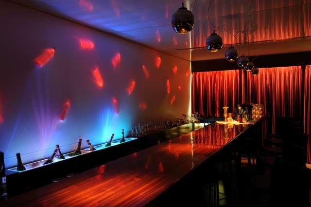 Photo du bar de l'auberge du port avec en fond mur avec éclairage graphique