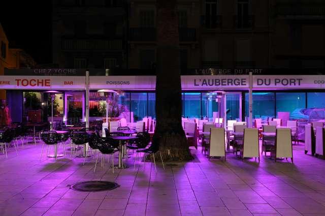 Photo de la deventure et terrasse de l'auberge du port avec un eclairage violet