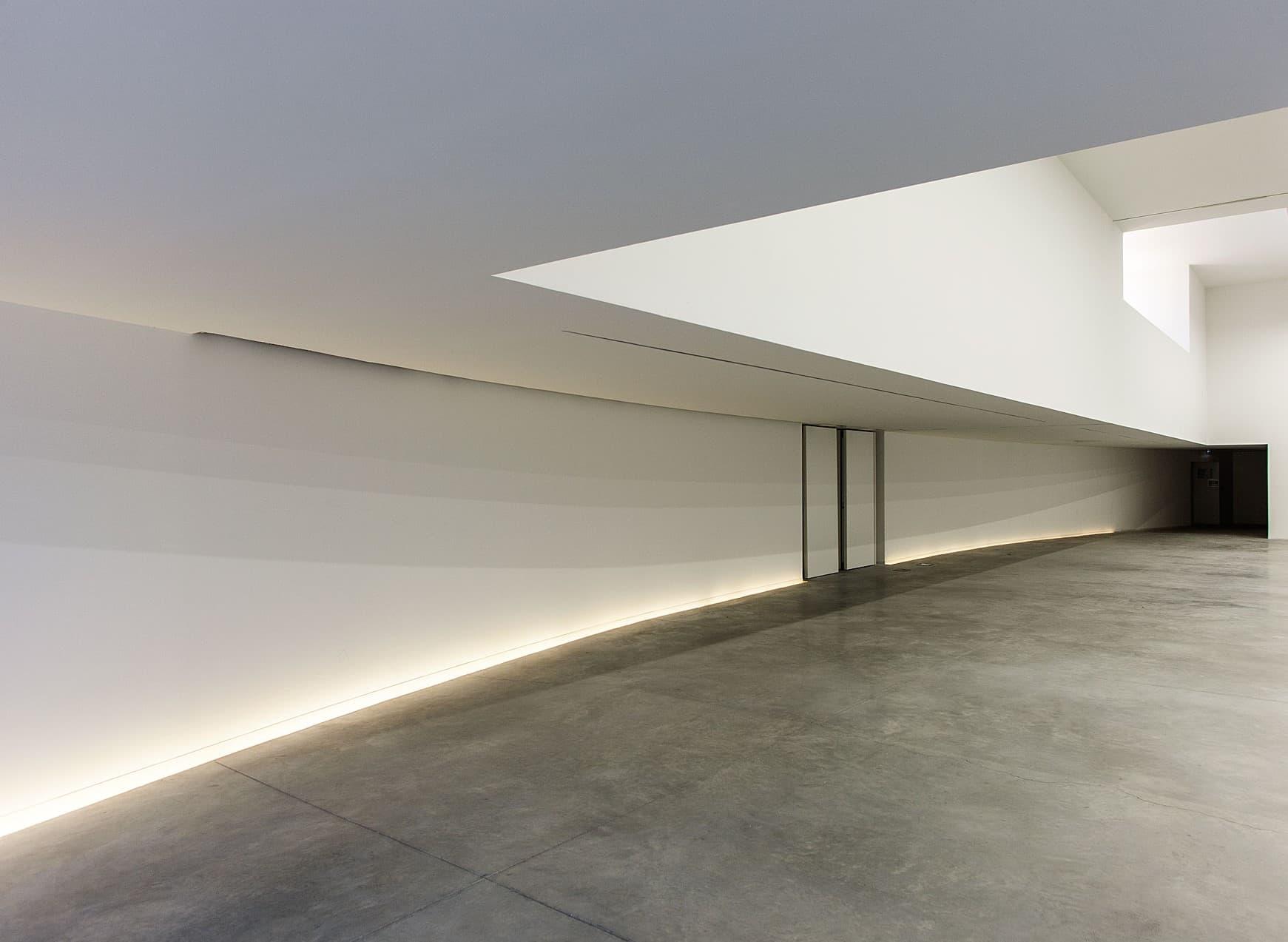 couloir lumineux sur un mur bétonné de la salle polyvalente e la duranne