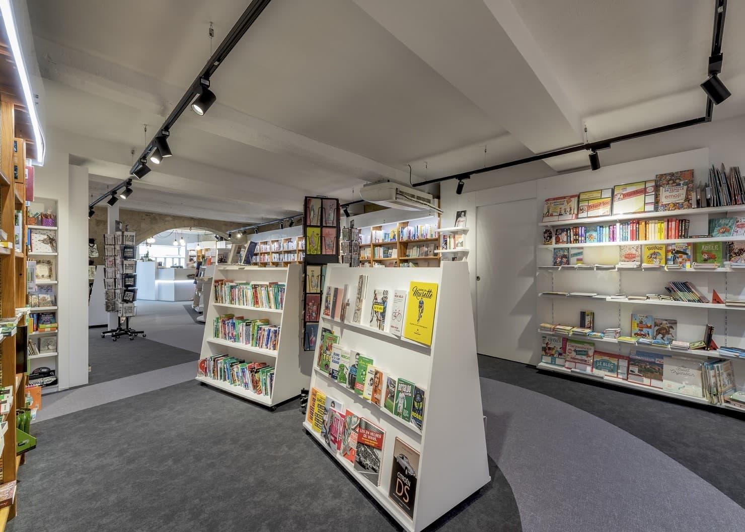 Vue de l'ensemble de l'éclairage dans Spots sur un rails magnétiques face à une bibliothèque de la librairie Mot à Mot