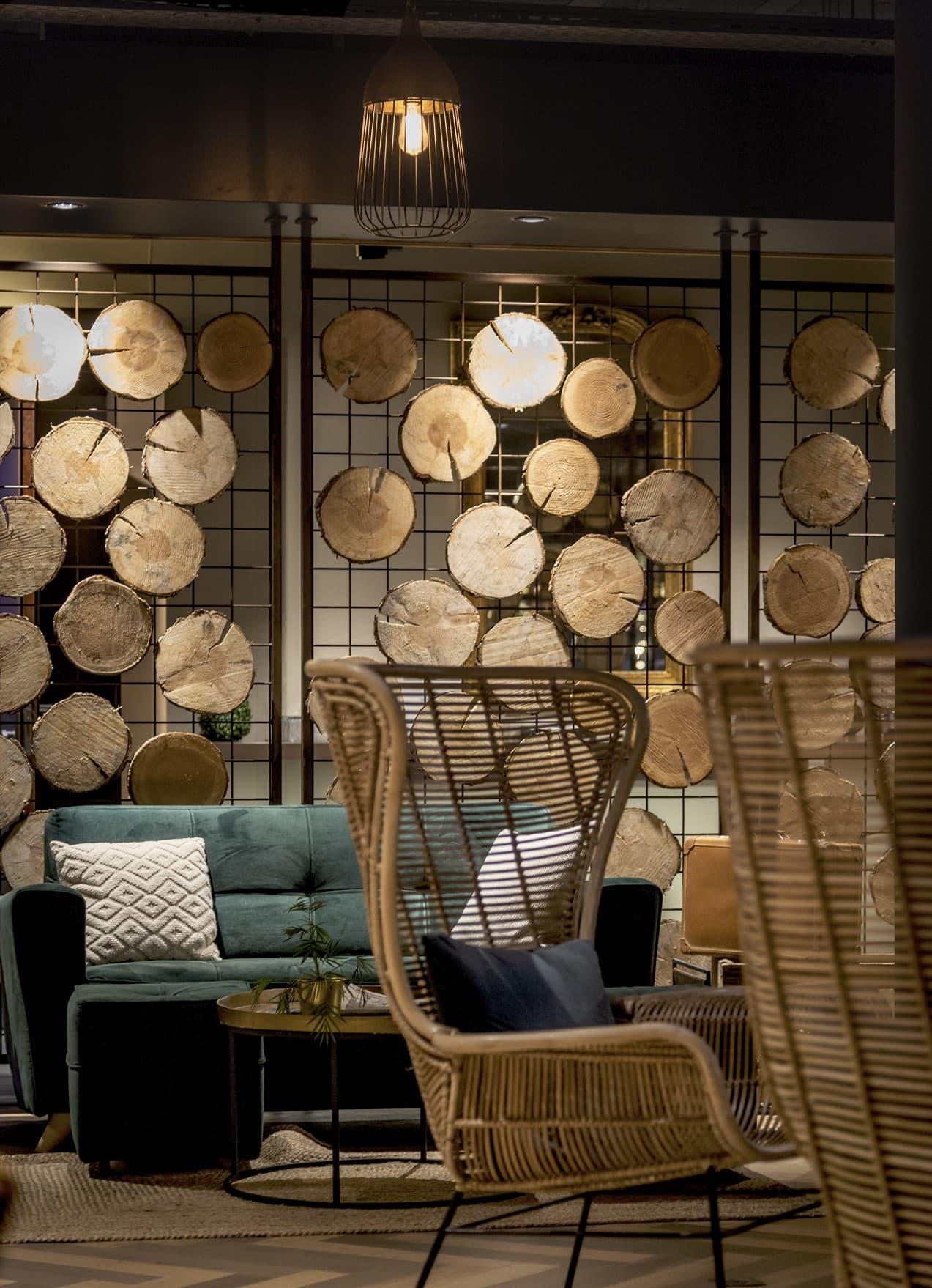 Panneau en fer et rondin de bois éclairé par des spots dans le Novotel Avignon