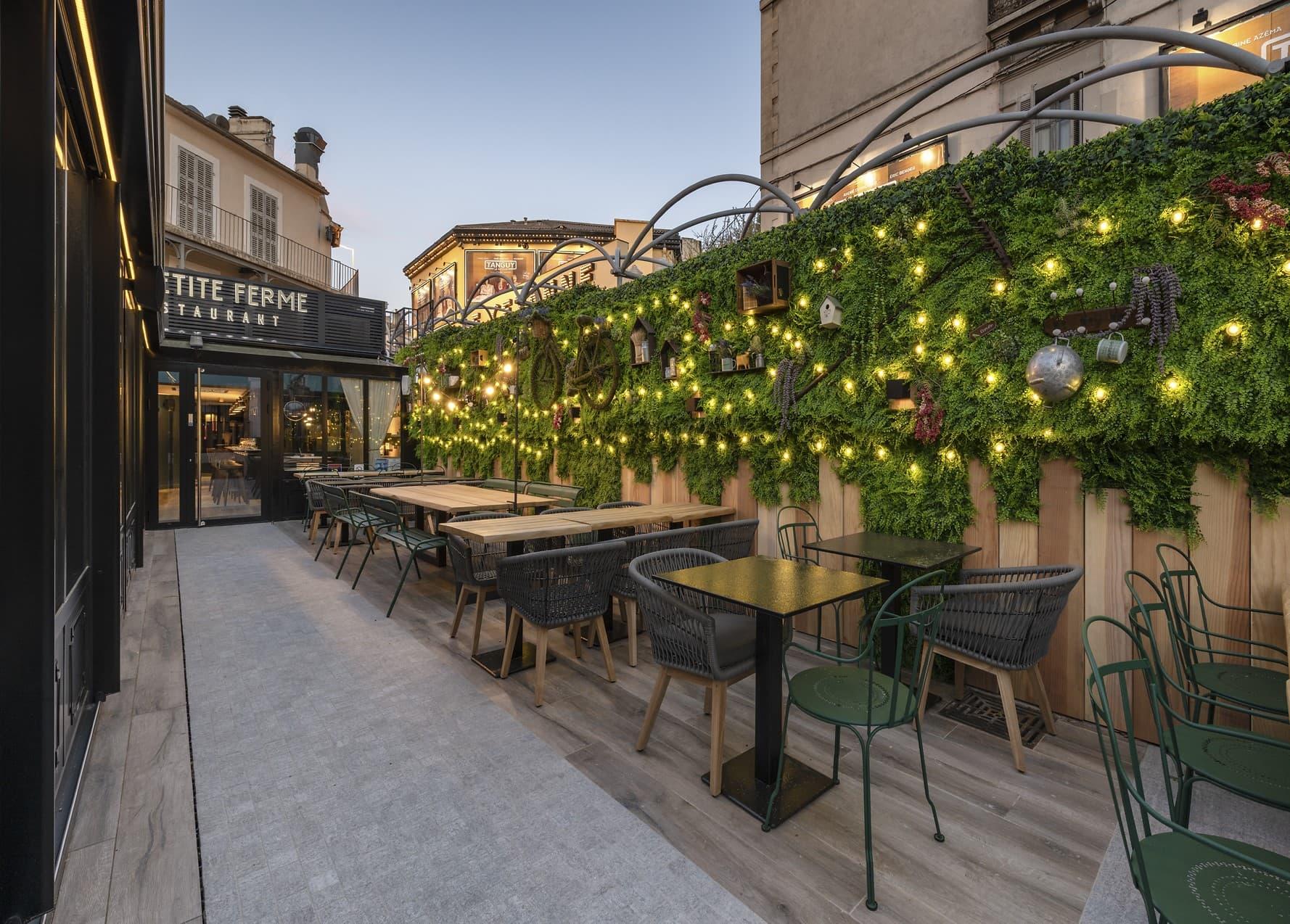 Guirlande de LED dans le mur végétal sur la terrasse du restaurant La Petite Ferme