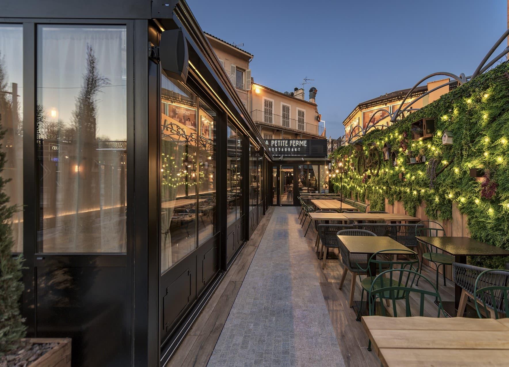 Eclairage extérieur de nuit du mur végétal et de la terrasse du restaurant la Petite Ferme