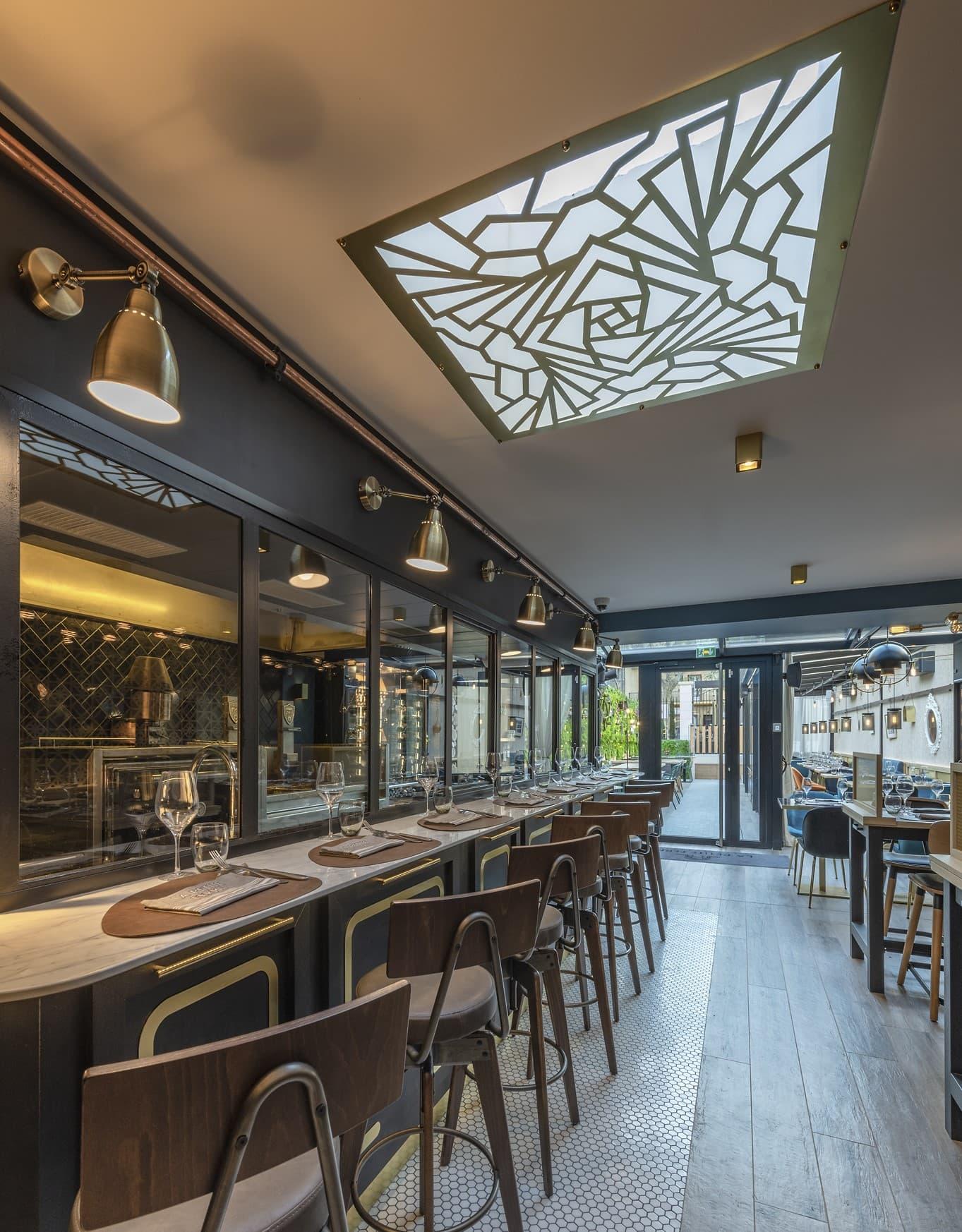 Focus sur les appliques murales et suspensions entourant le puit de lumiaire de style art déco dans le restaurant La Petite Ferme