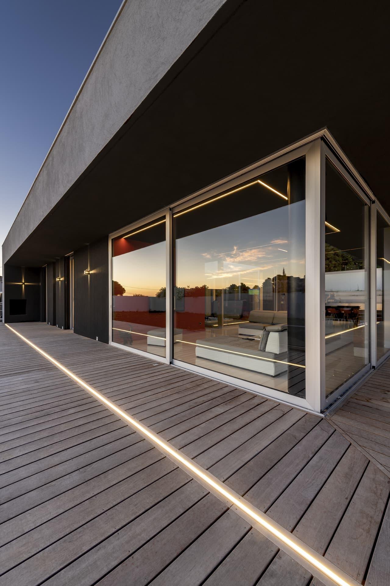 Ligne lumineuse encastrée dans la terrasse extérieure devant la baie vitrait du salon de la villa privée Juliette