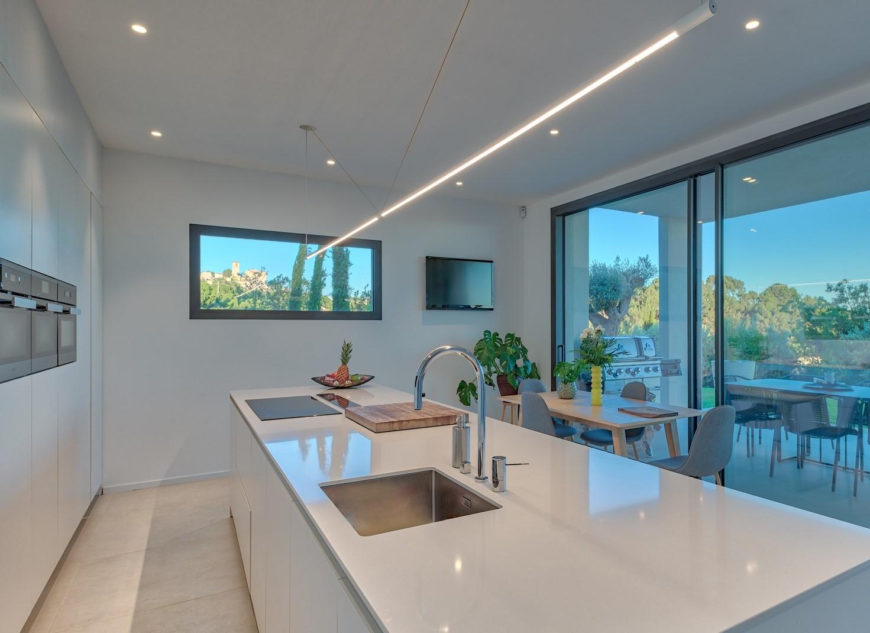 Spots encastrés et ligne lumineuse suspend dans la cuisine de la villa privée Bravo