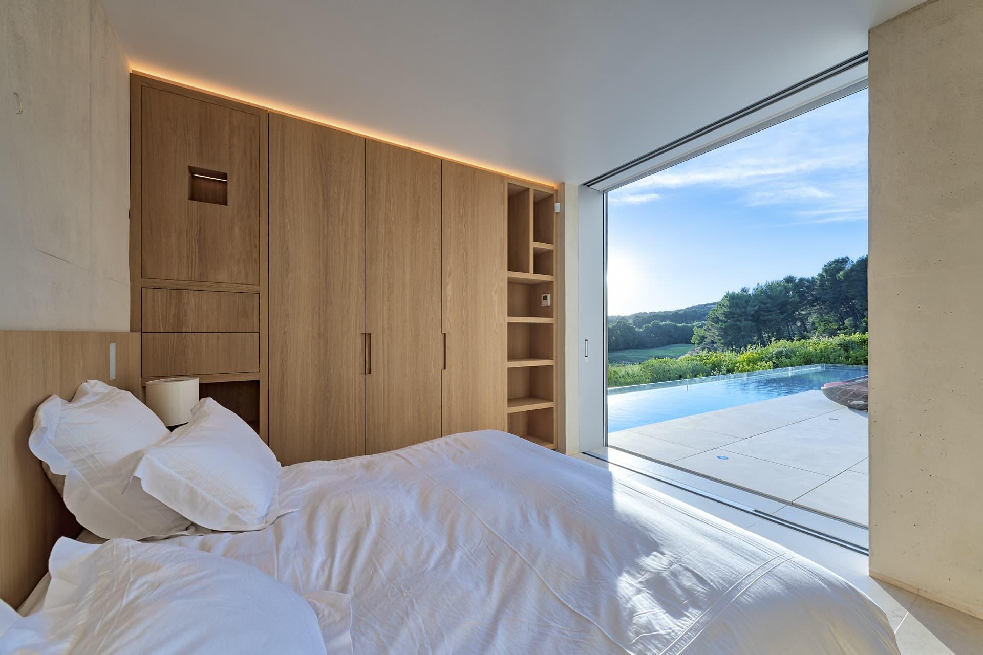 Gorge lumineuse au dessus d'une armoire dans une chambre ouverte sur la piscine dans la villa privée Sigma