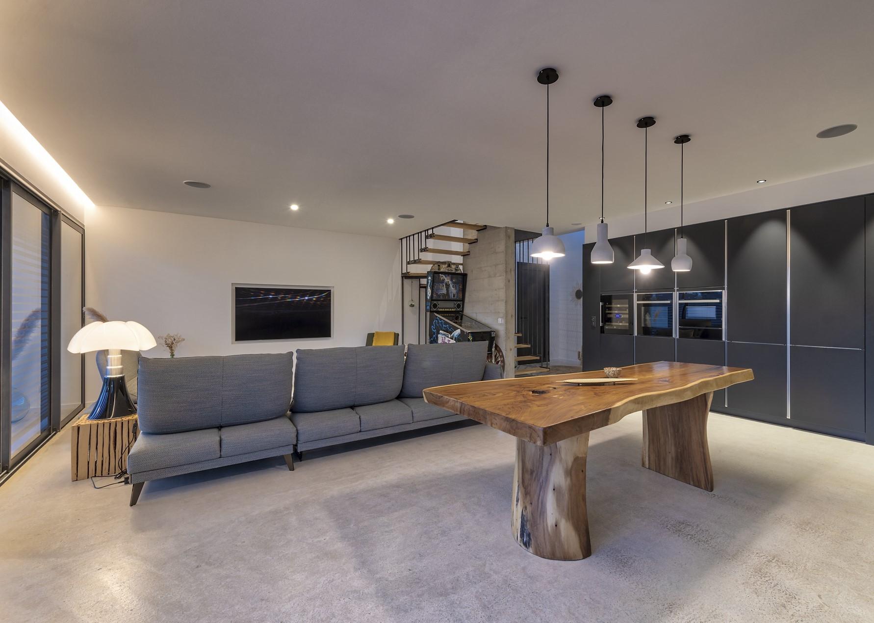 Salon et salle à manger avec un alignement de quatre suspension au dessus de la table de salle à manger dans la villa privé Zeta
