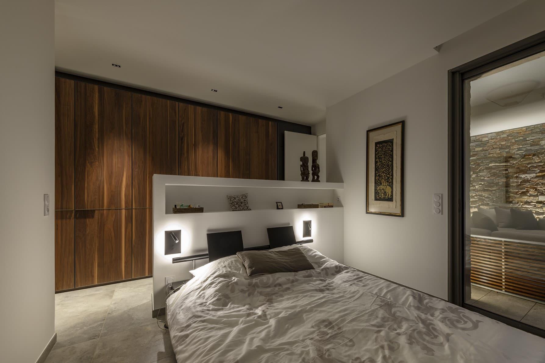 Chambre de la villa avec desapplique de chaque côté du lit