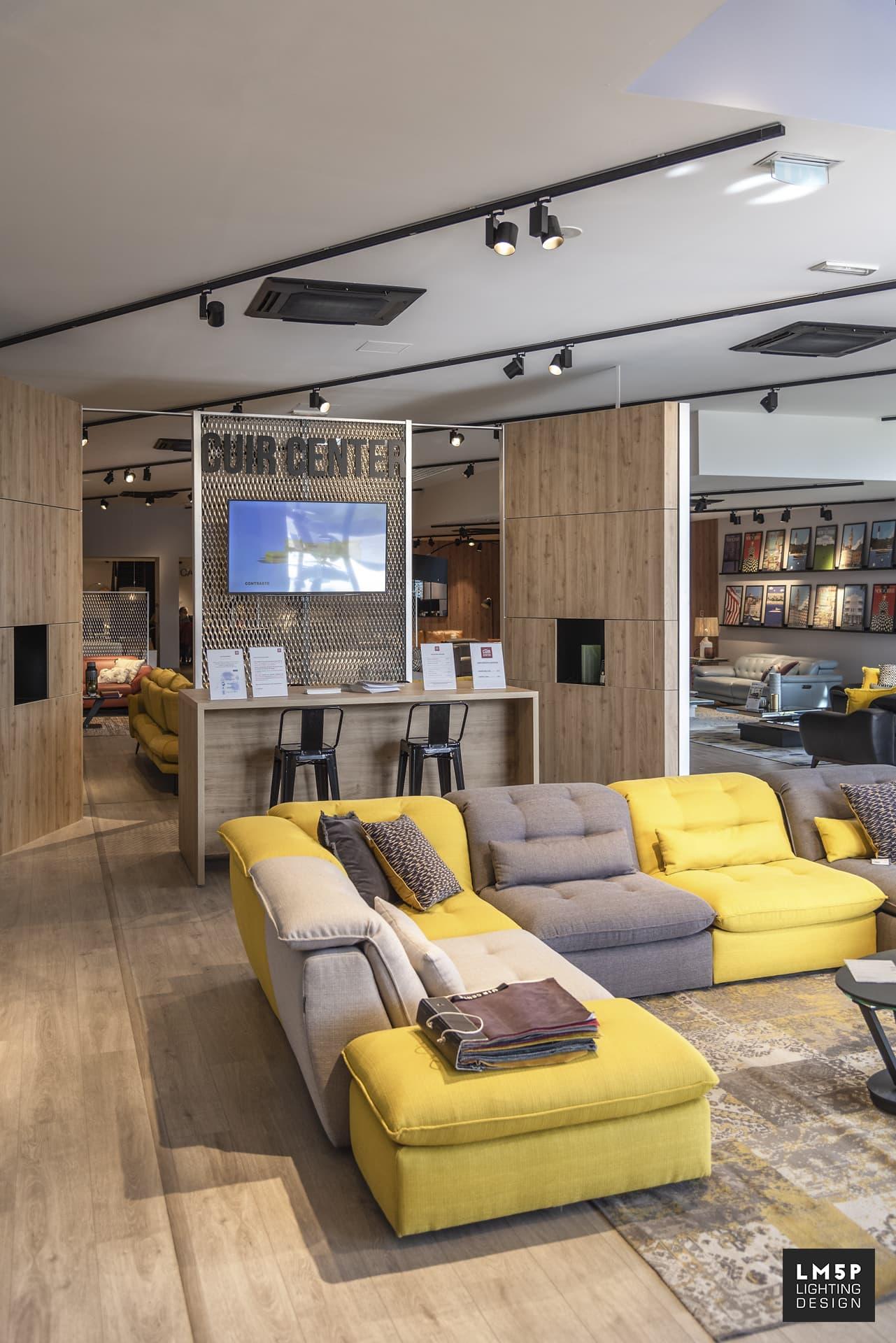 canapé bicolore (jaune et gris) sous des spots de chez nobile dans le magasin cuir center