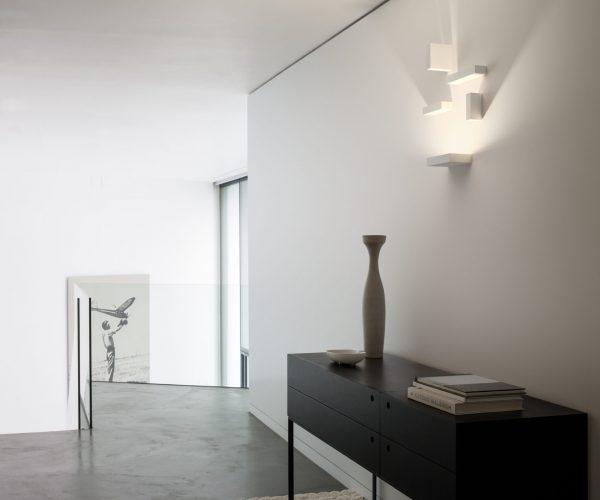 applique set sur un mur blanc au dessus d'une console noir